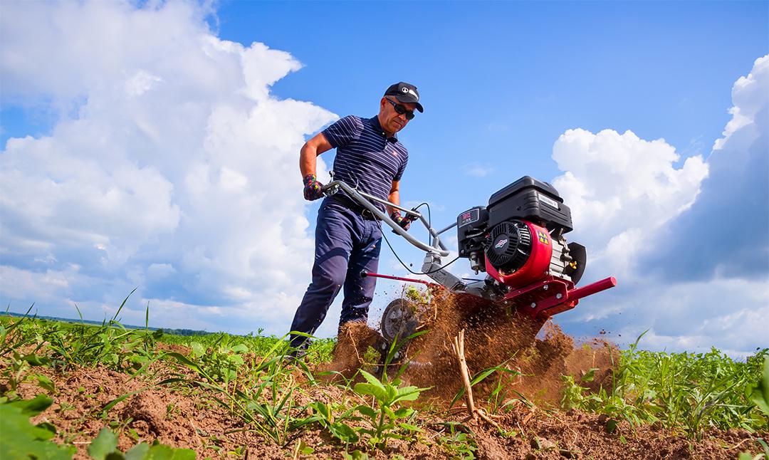Мужчина обрабатывает землю культиватором