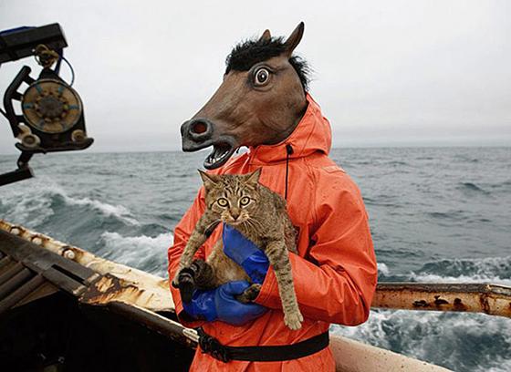 Человек в маске лошади с котом на рыболовецком судне